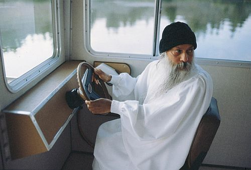 osho at the steering-wheel of a boat